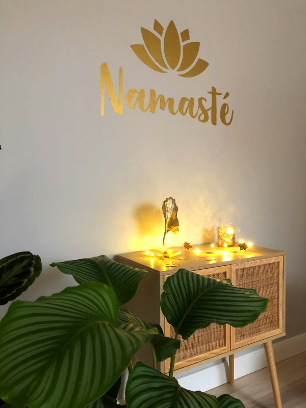 Namasté mit Kerzen und Pflanze