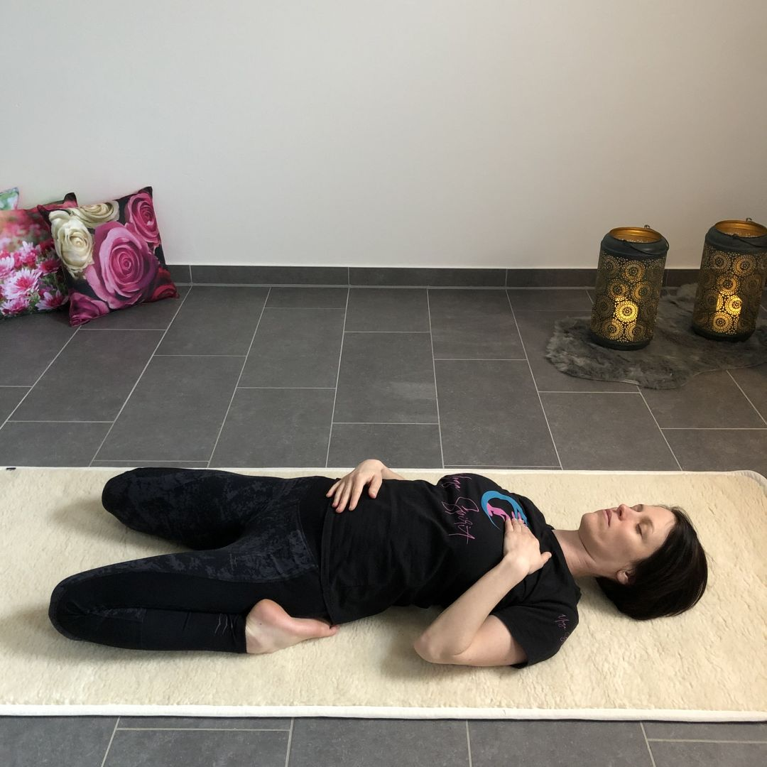 Yin Yoga Position liegend Hand auf Bauch und Herz